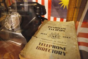 An old telephone directory next to an old fashion phone