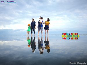 a family poses for photos in Malaysia's 'Mirror in the Sky'