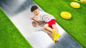 A child glides smoothly down the Sliding Mountains