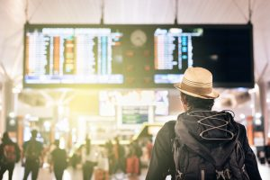 young traveler or tourist looking at airport time board