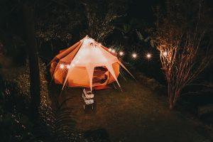 Camping tent surrounded with trees at night