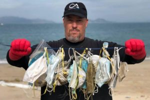 Man clears up litters of discarded face masks on a beach in Hong Kong