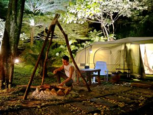 A man tries to set a campfire outside his tent at Lost World of Tambun's glampsite
